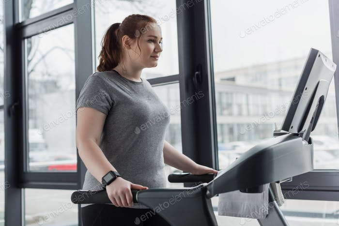 Obese girl running on treadmill in gym