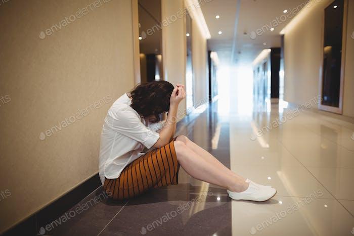 Sad female business executive sitting in corridor