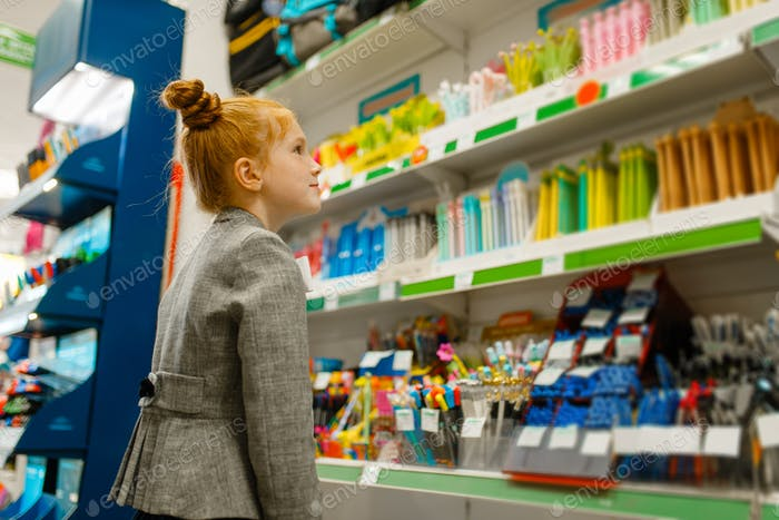 School girl choosing a pencil in stationery store
