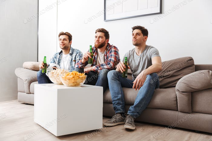 Portrait of three concentrated young men watching football