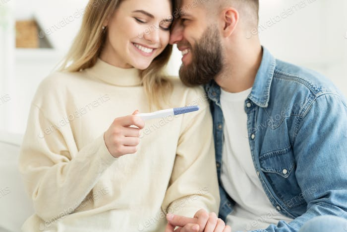 Happy couple checking pregnancy test, positive result