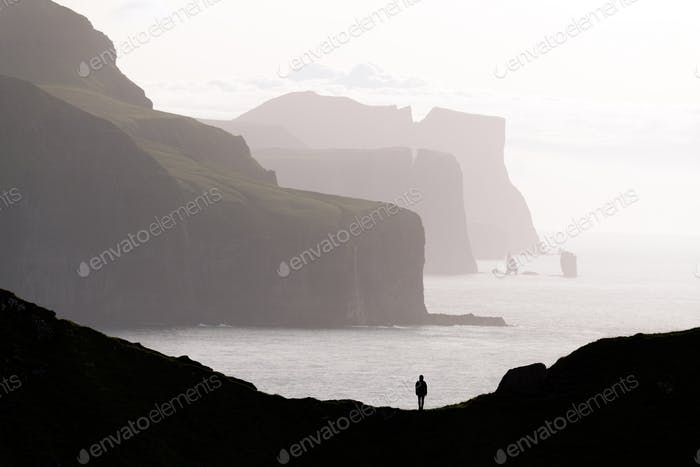 Man silhouette on background of famous Risin og Kellingin rocks