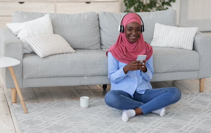 Islamic Women Leisure. Religious Black Lady In Hijab Listening Music At Home