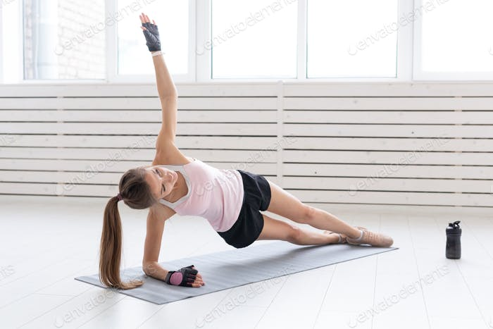 Sport, yoga and people concept - young woman is doing fitness. She is pressing on the floor in gym