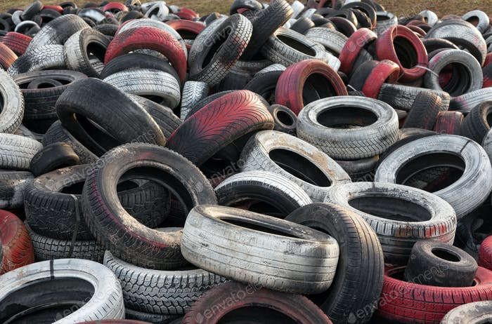 Variety of red white and black waste car tires piled in a big pile