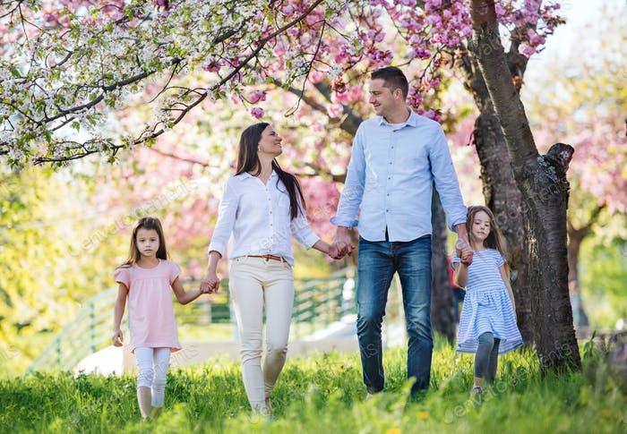 Young parents with small daugthers walking outside in spring nature