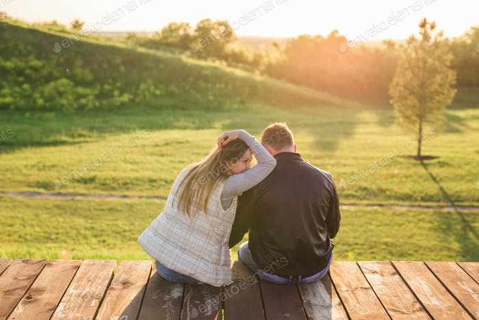couple hugging on a pier in nature back view