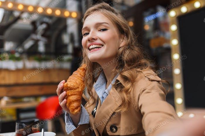 Pretty joyful girl in trench coat happily looking in camera taki