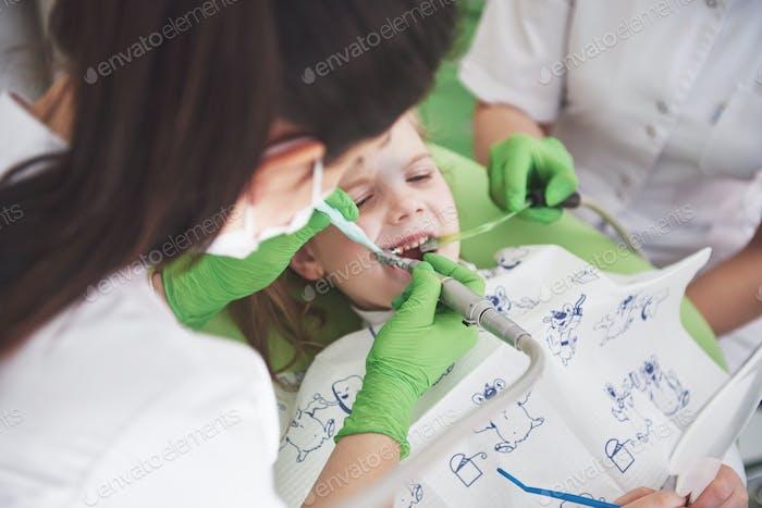 pädiatrische Zahnarzt und Assistent machen Untersuchungsverfahren für lächelnd niedlichen kleinen Mädchen