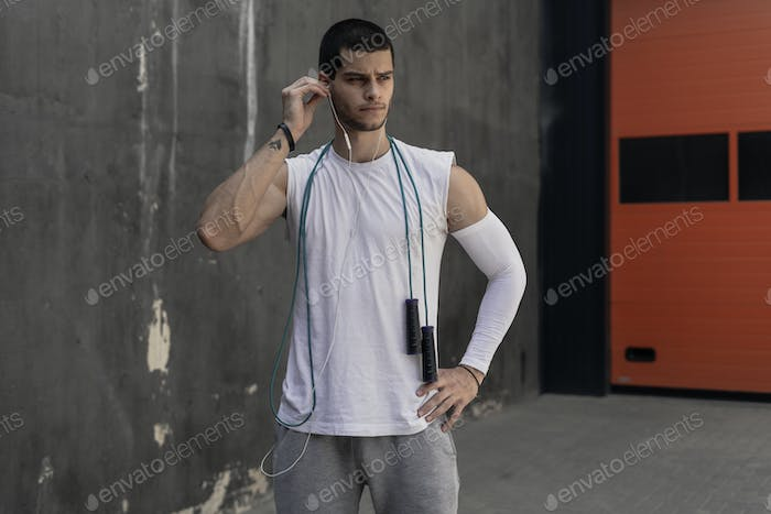 Portrait athletic man getting ready to rope jumping while firing earphones