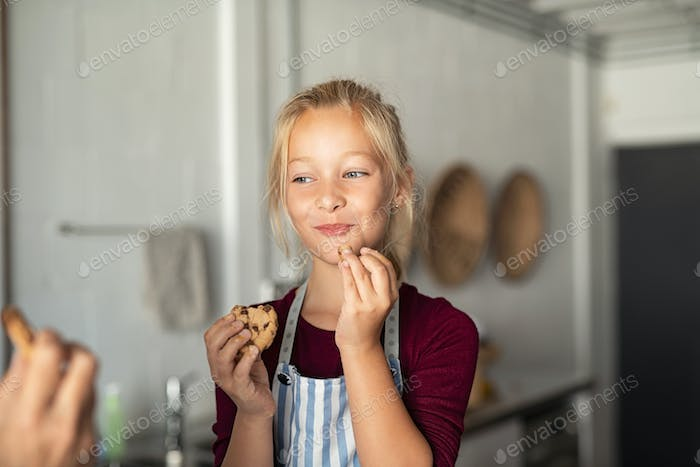 Funny cute girl eating chocolate cookie