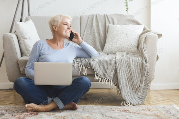 Joyful elderly business lady talking with clients, working at home