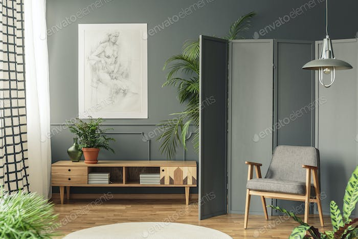 Retro armchair against a gray screen next to a drawing hanging o
