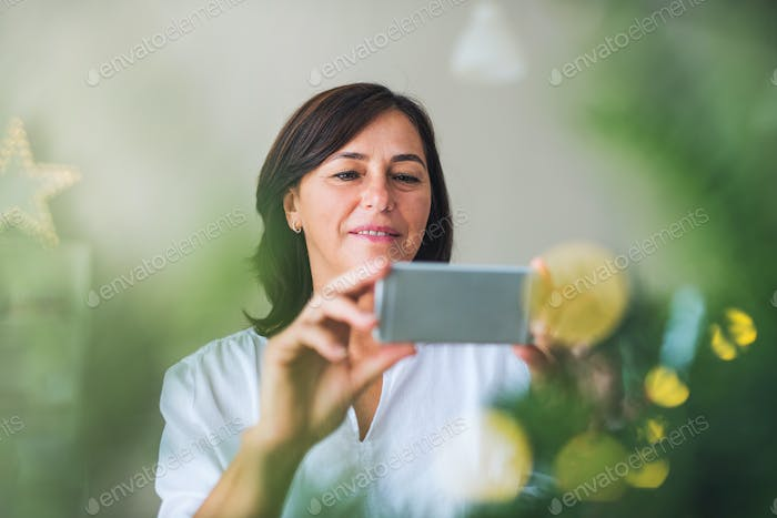 A senior woman with smartphone by a Christmas tree at home, taking selfie.