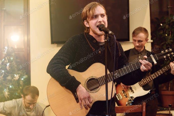 stilvoller Sänger mit Bart, der lyrische Song auf der Bühne mit seiner Band