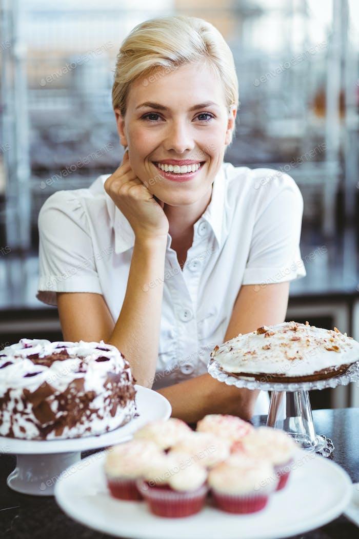 Happy pretty woman preparing plate of cake