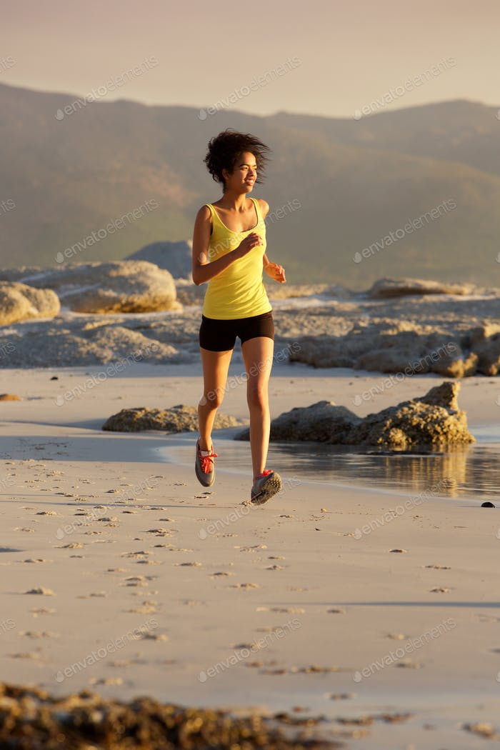 Smiling young fitness woman running on beach