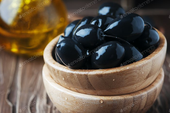 Black olive and olive oil on the wooden table