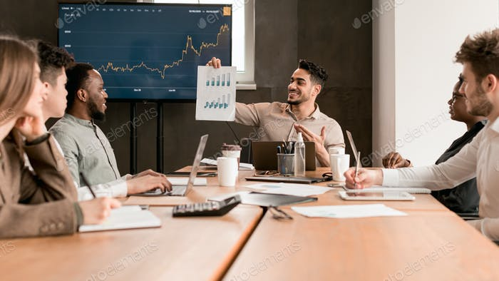 Employee showing paper with graph diagram, sitting at desk