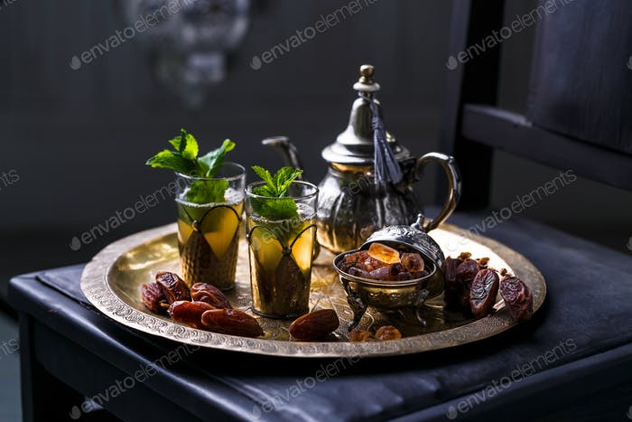 Moroccan mint tea in the traditional glasses on a tray and kettle