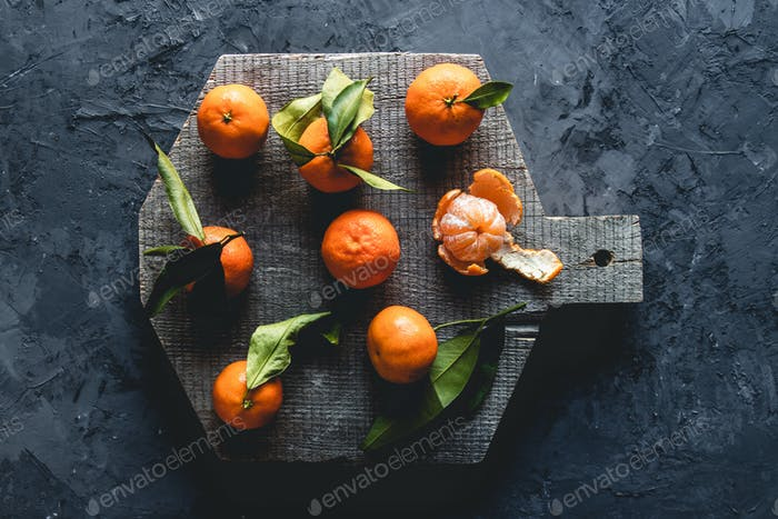 Group of three whole one piece of fresh orange mandarin on wooden board. eco vegetarianism. PNOV2019