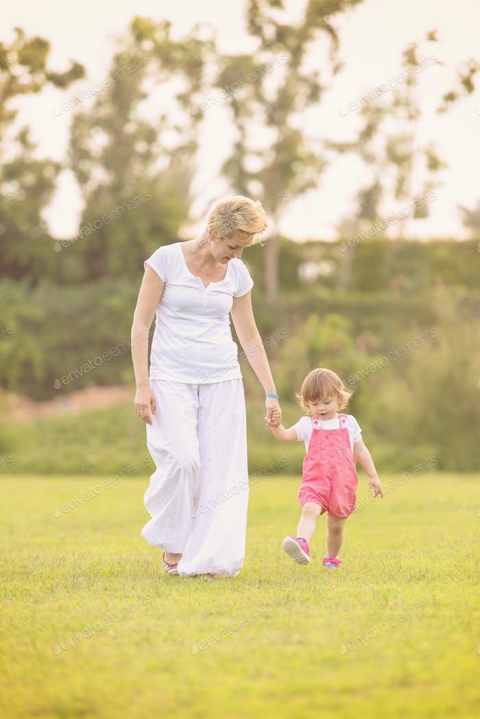 Mutter und kleine Tochter spielen bei Hinterhof