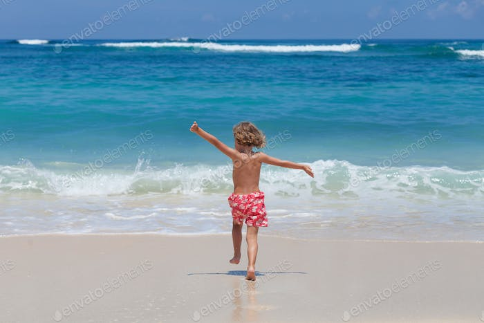 Happy little boy running on the beach