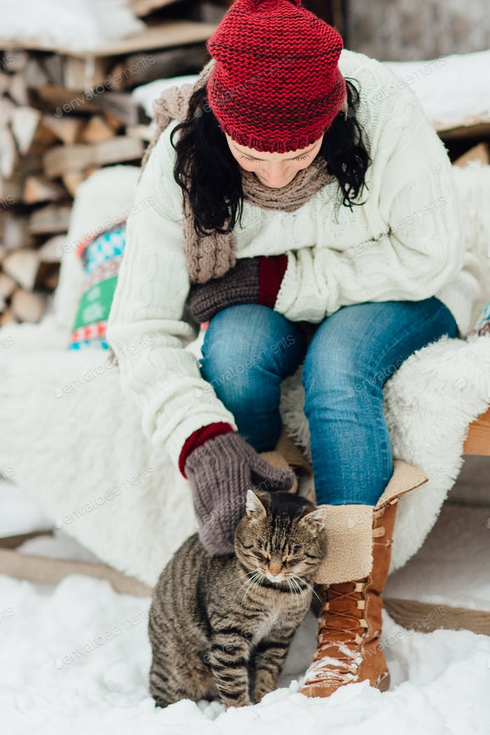Cropped image of a woman stroking a cat in the snow