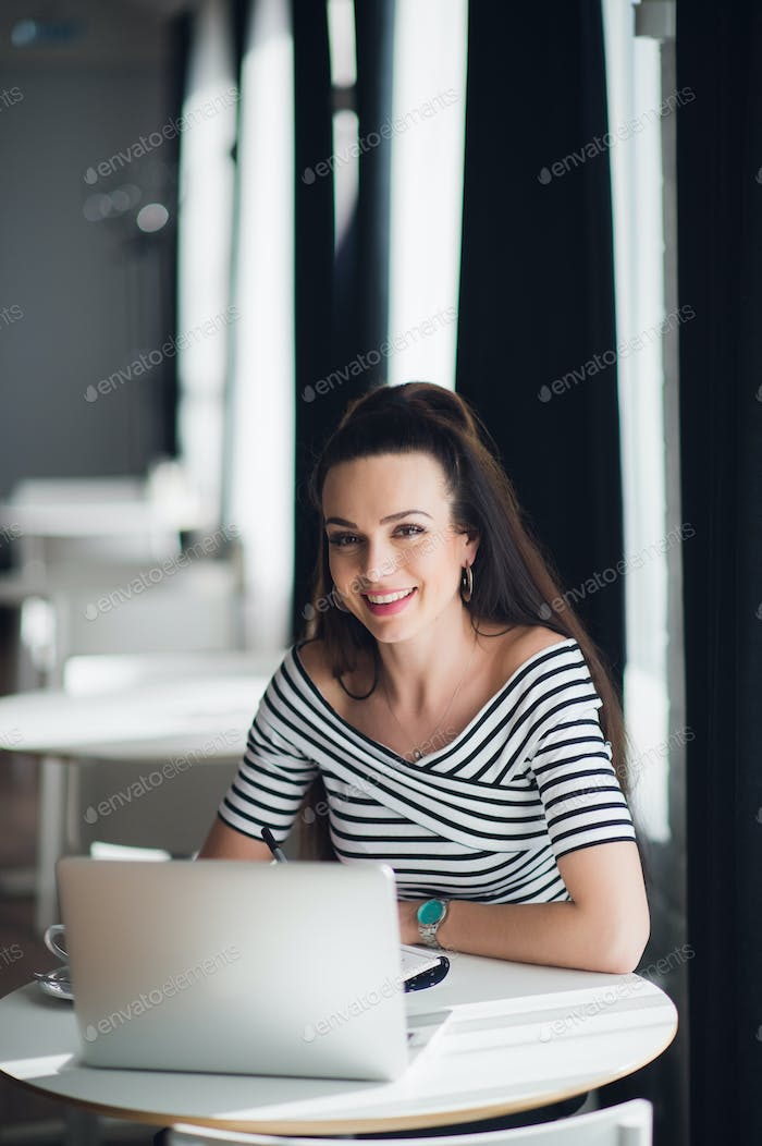 Picture of smiling woman using laptop in a cafe and looking at the camera.