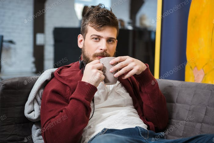 Relaxed boy sitting on sofa and drinking coffee