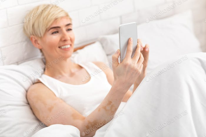 Happy mature woman having video call by cellphone