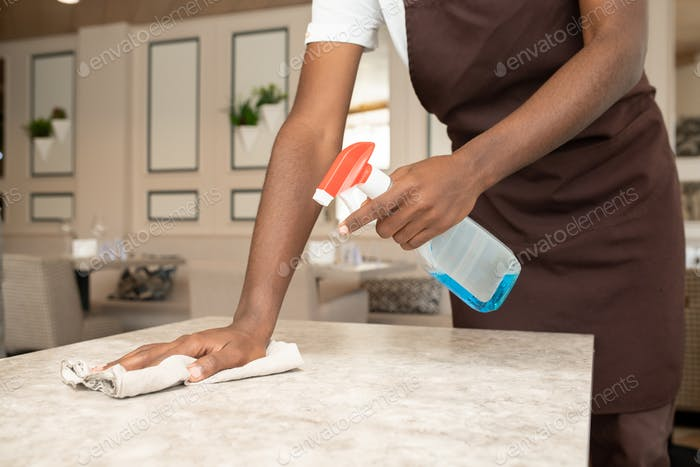 Hands of young waiter spraying detergent on table while cleaning it with duster