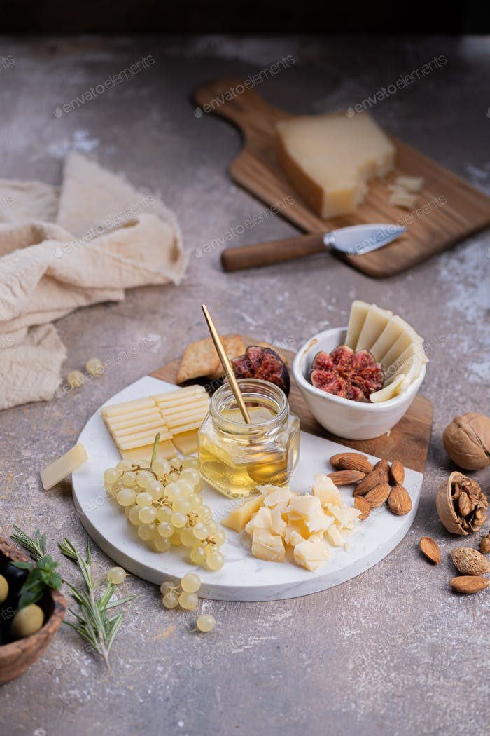 Assorted cheeses on marble board with figs, nuts, grapes and honey