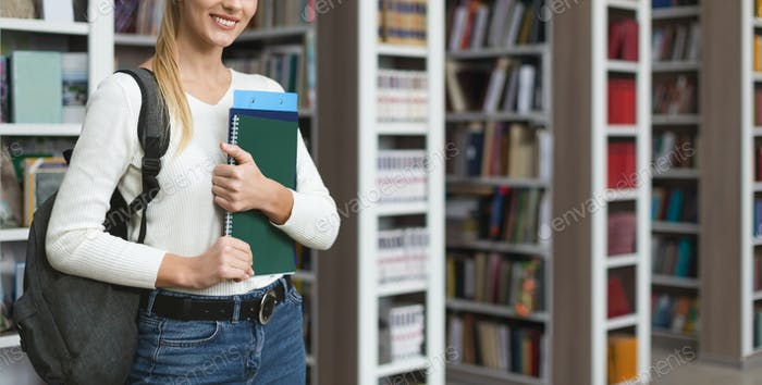 Young caucasian girl standing next to bookshelves in library