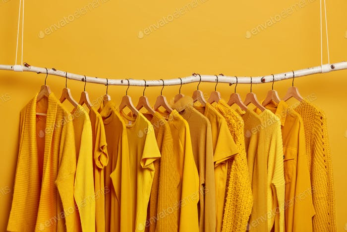 Rack with yellow clothes after dry cleaning. Wardrobe with various outfits for different seasons. Wo