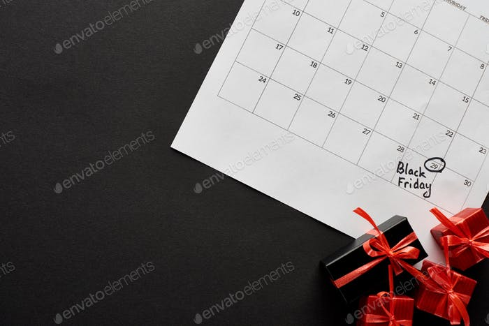Top View of Gift Boxes And Calendar With Black Friday Date on Black Background
