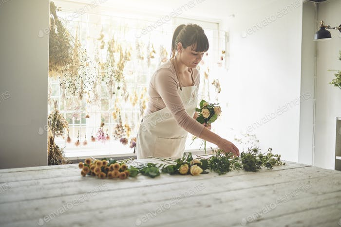 Young florist working at a table in her flower shop