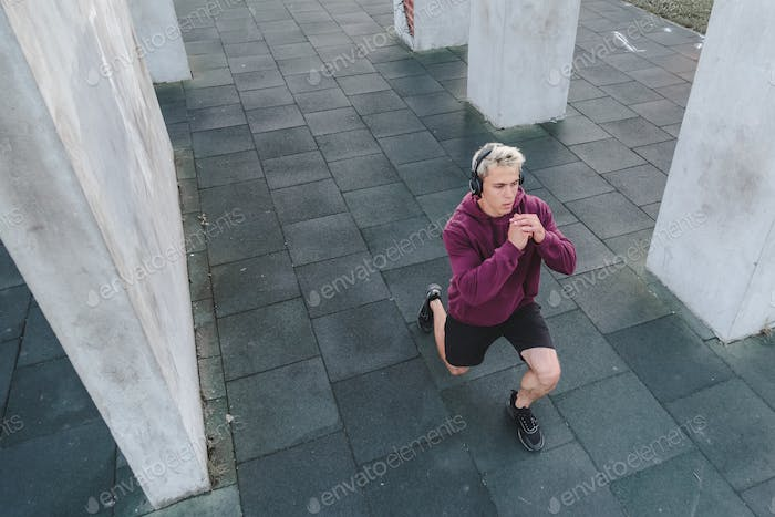Young athletic man with headphones listen to music and warming up outdoors. Do lunge
