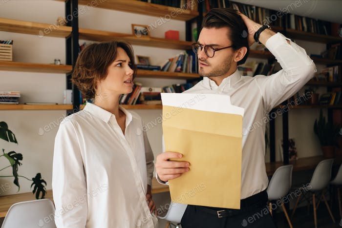 Disappointed business colleagues with envelope letter sadly looking at each other in office