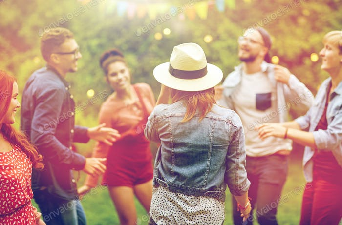 happy friends dancing at summer party in garden