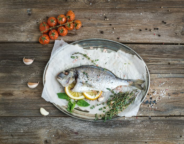 Roasted dorado or sea bream fish with vegetables, herbs and spices