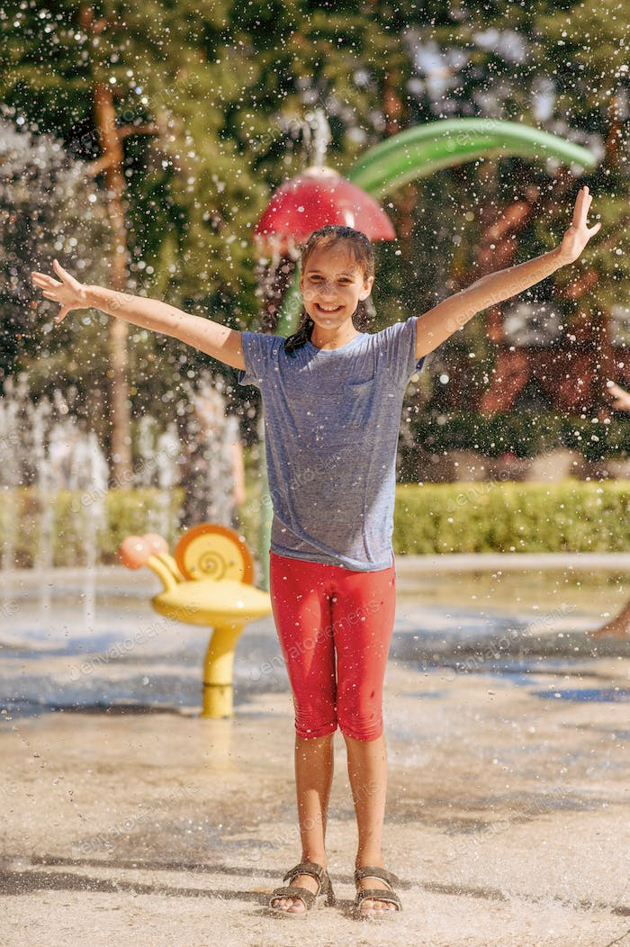Little funny girl in splashes on water playground