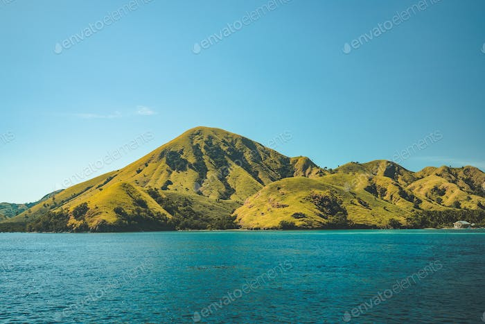 Greens covered hills washed by calm ocean. Komodo