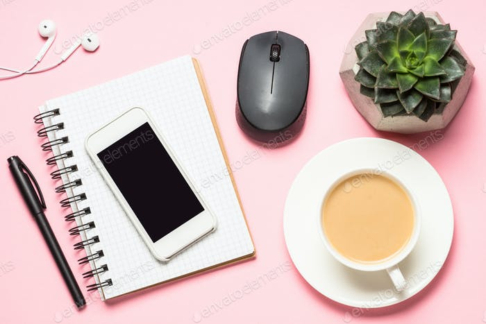 Freelance workplace with notepad, coffee cup, succulent and mouse on pink