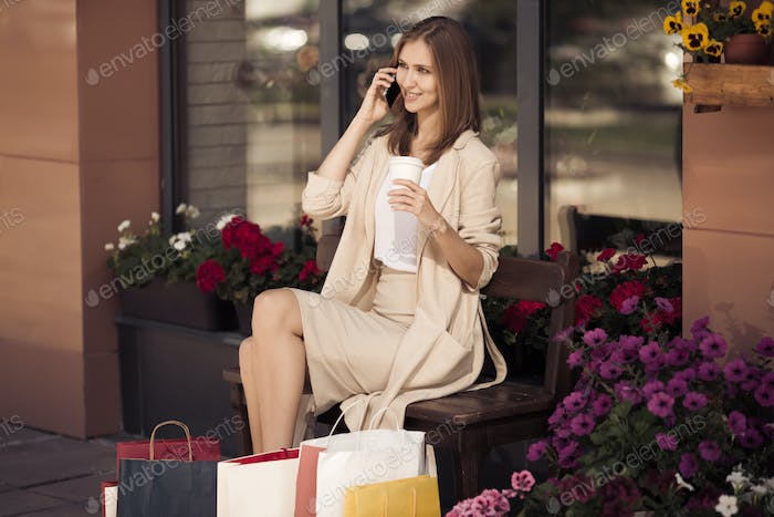 Woman With Shopping Bags Sitting On Bench And Talking Phone.