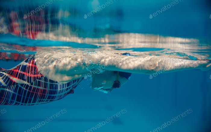 Female swimmer swimming in pool, underwater view