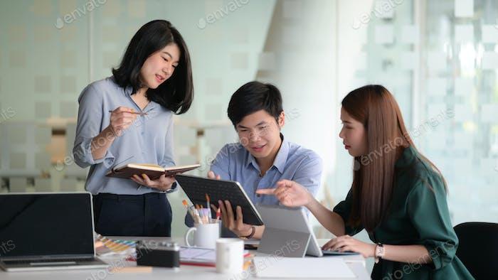 Von professionellen Designern mit Laptop und Geräten sind Brainstorming, um Projekte zu erstellen.