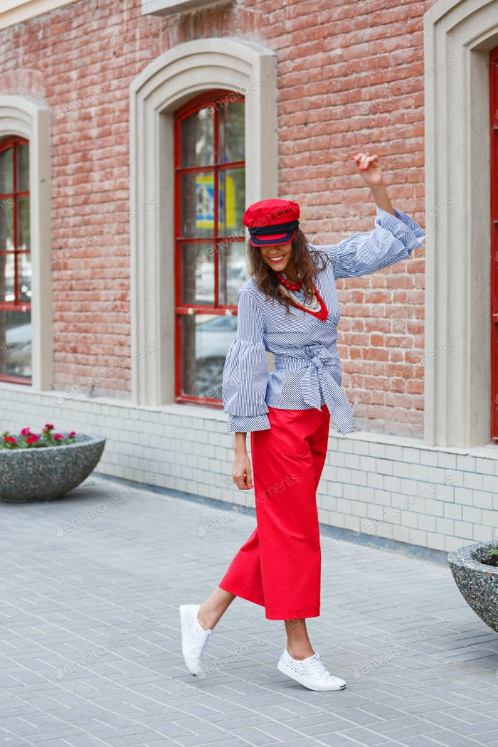 Stilvolle brünette Mädchen in einer gestreiften Bluse gekleidet, rote weite Hosen und eine rote Mütze Posen in der Stadt