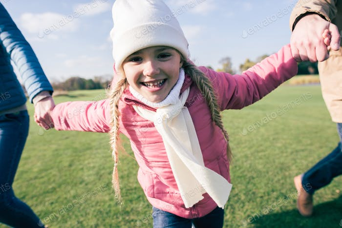 Close-up portrait of adorable smiling girl holding hands and having fun with parents on green meadow