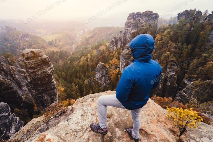 Wanderer in Outdoor-Kleidung genießen den Sonnenuntergang auf Bergspitze mit herrlichem Blick auf Klippen Grat